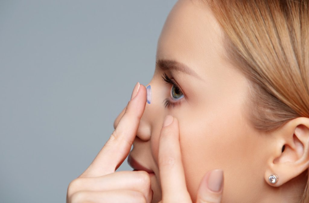 Woman inserting a toric contact lens into her eye
