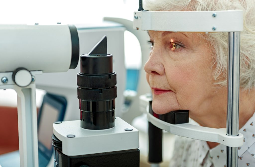 An older woman having her eyes examined by an optometrist