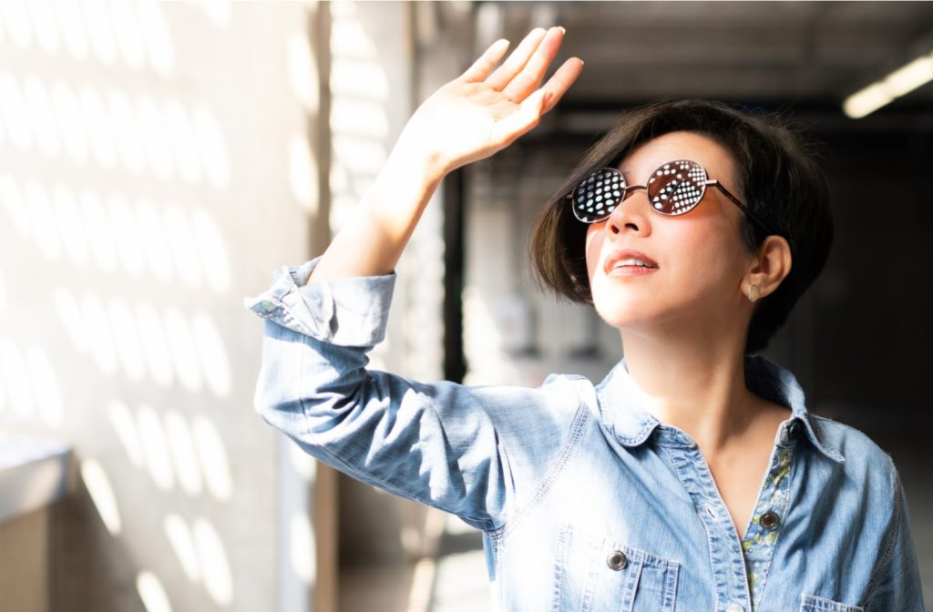 Woman using her hand to protect herself from sun glare that comes through the blinds.