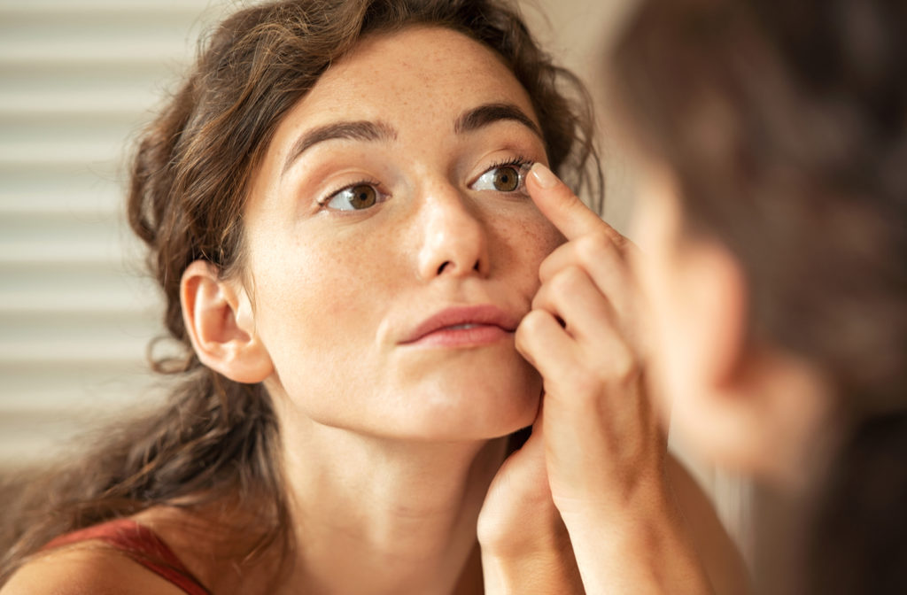 Young woman trying on contact lenses as she looks at self in mirror.