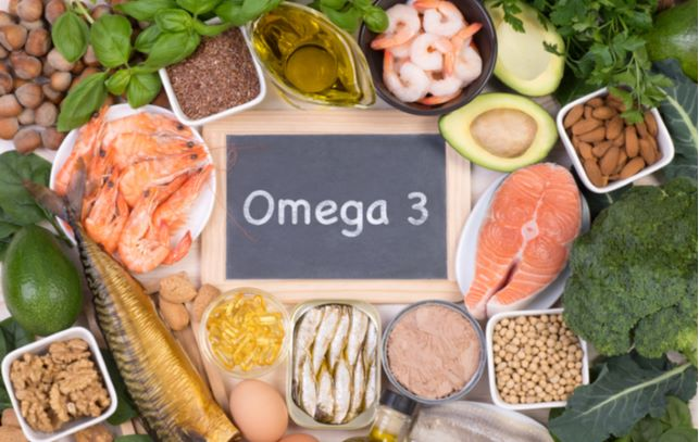 """Wooden board with """"omega 3"""" written on it with food surrounding it"""