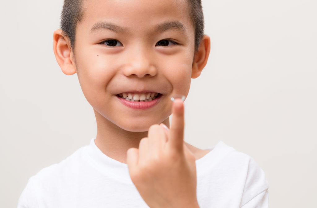 Young boy holding contact lens to help control myopia progression